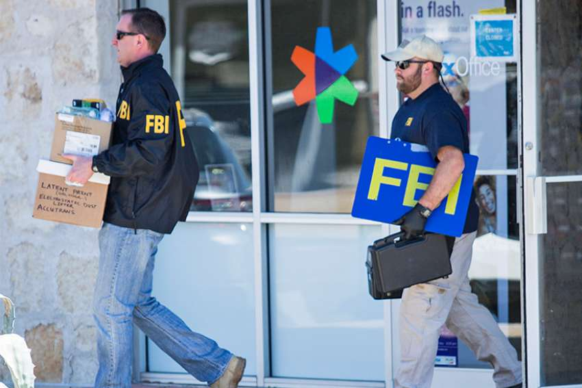 "FBI agents are seen carrying items out in paper bags and boxes March 20 from a FedEx store in Austin, Texas, after a fifth bombing. ""These appalling attacks have killed and injured innocent people, young adults, and children who were in their homes, bicycling on the street, and working at their jobs,"" Archbishop Gustavo Garcia-Siller of San Antonio and Bishop Joe S. Vasquez of Austin said in a March 20 statement."
