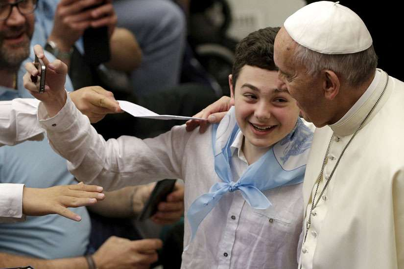 "A child takes a selfie with Pope Francis. The Holy Father's willingness to be open and accessible is one of the ways, that Francis has proven that he is ""real"" as Robert Brehl summarizes."