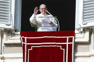 Pope Francis waves as he leads the Angelus from the window of his studio overlooking St. Peter's Square Dec. 9 at the Vatican.