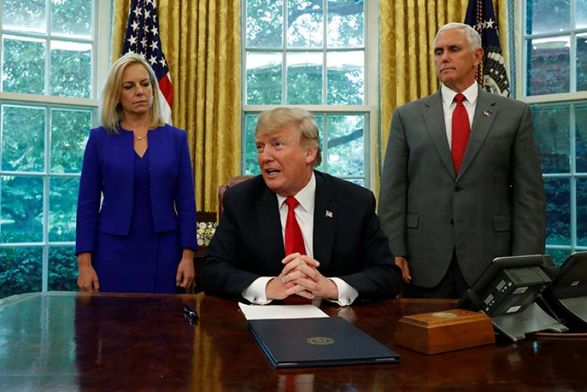 President Donald Trump is seen with with Secretary of Homeland Security Kirstjen Nielsen and Vice President Mike Pence at the White House June 20 prior to signing an executive order to halt the separation of families.