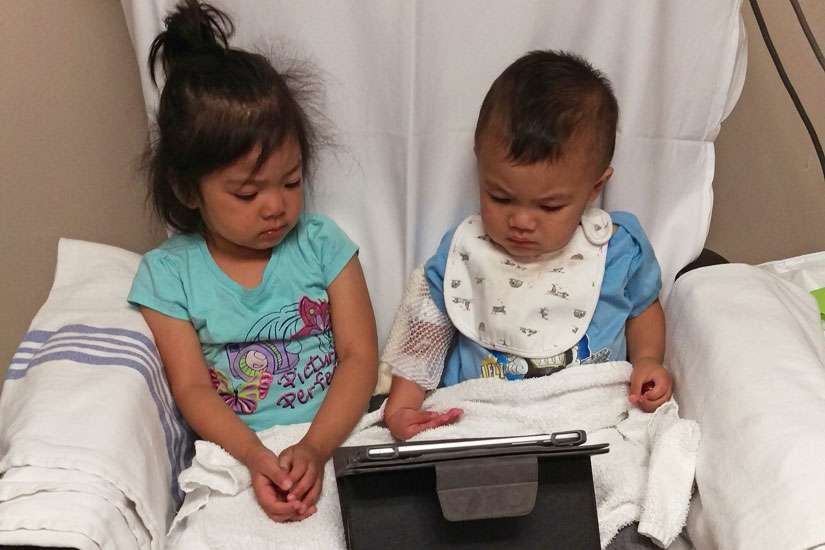 Timothy Rafanan with his sister Emily playing with an iPad as he receives his regular blood transfusion.