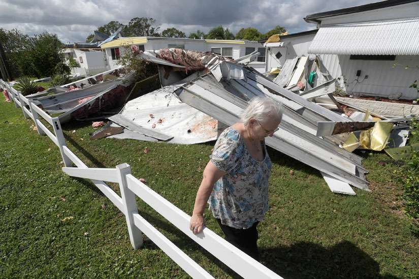 Cherie Monroe pauses after looking at the roof of her home Oct. 9 in the aftermath of Hurricane Matthew in Port Orange, Fla.