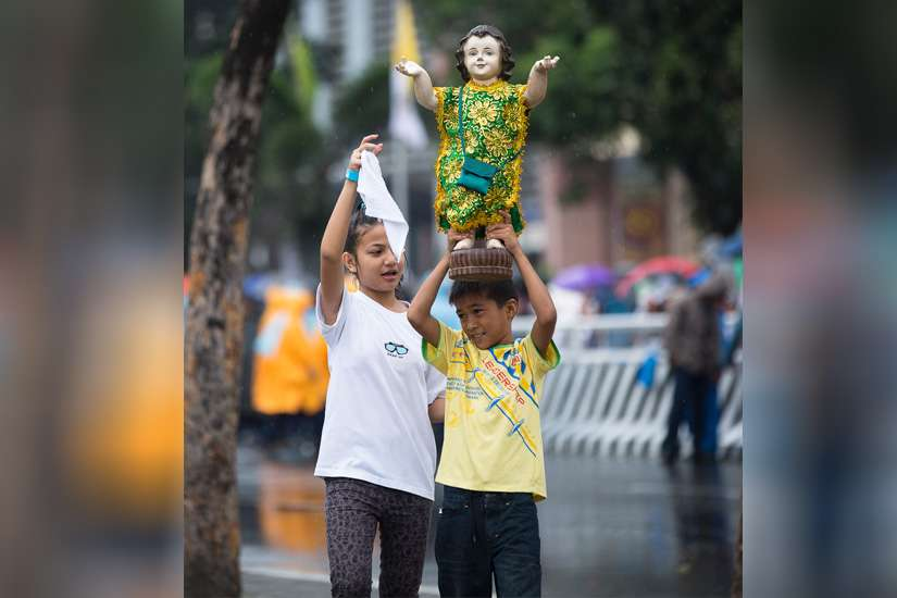 A boy carries a Santo Nino statue in Manila, Philippines, prior to the closing Mass in Rizal Park Jan. 18.