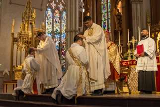 Over 200 priests in attendance for the ordination laid their hands on Alexander MacDonald and Raymond So, May 12, at St. Michael's Cathedral Basilica.