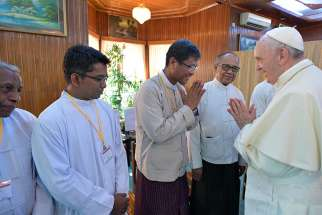 Pope Francis greets men during a small informal meeting with a variety of religious leaders Nov. 28 at the archbishop's residence in Yangon, Myanmar.