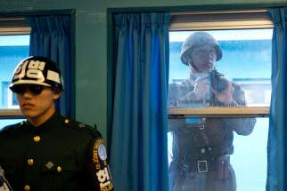 A North Korean soldier takes photos through the window of one of the conference rooms in the Joint Security Area between North and South Korean in 2012.