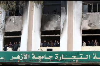 In this Dec. 29, 2013, file photo, Egyptian students look out the windows of a faculty building at Cairo's al-Azhar University one day after student supporters of the Muslim Brotherhood set it on fire in Cairo, Egypt. The Vatican's interreligious council invited Ahmad el-Tayeb, the grand imam of al-Azhar University, to travel to the Vatican and meet with Pope Francis.
