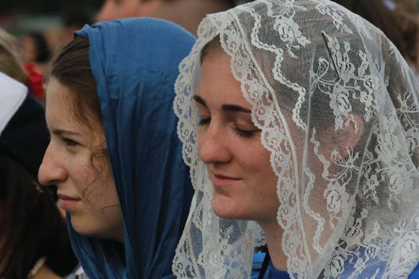 A young woman prays during the opening Mass for World Youth Day at Blonia Park in Krakow, Poland.