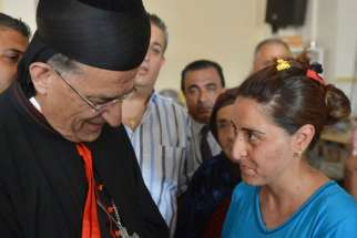 Lebanese Cardinal Bechara Rai, Maronite patriarch, who headed a delegation of Mideast patriarchs, blesses a baby Aug. 20 in Irbil, Iraq. The blessing took place in one of the churches housing the more than 100,000 Christians and minorities displaced in t he country by the advance of Islamist militants.