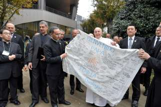 Pope Francis receives a welcome banner from the theology faculty at Jesuit-run Sophia University in Tokyo Nov. 26, 2019.