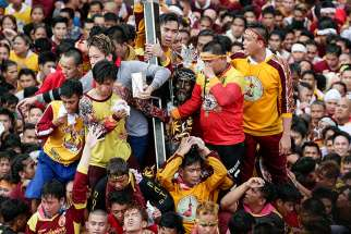 Pilgrims climb to touch the Black Nazarene during Jan. 7 procession in Manila, Philippines. The wooden statue, carved in Mexico and brought to the Philippine capital in the early 17th century, is cherished by Catholics, who believe that touching it can lead to a miracle.