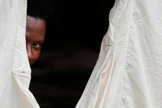 A Haitian refugee sticks his head out from a tent set up by the Canadian Armed Forces near Lacolle, Quebec, Aug. 10. Pope Francis released a statement Aug. 21 urging respect for the life and dignity of migrants and refugees.
