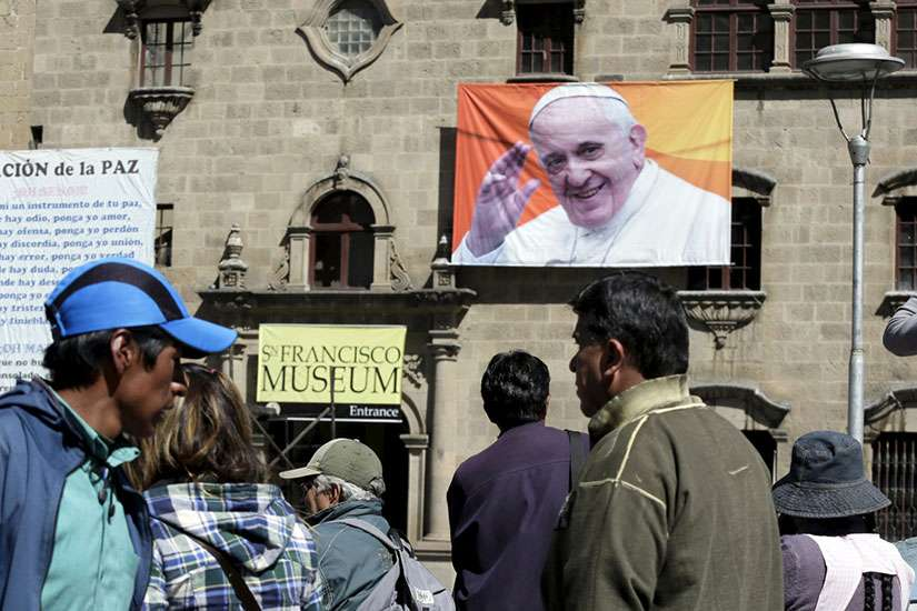 People walk past an image of Pope Francis in La Paz, Bolivia, June 30. The Pope will visit Bolivia July 8-10.