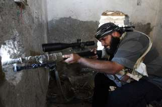 A Free Syrian Army fighter aims his weapon through a hole in a wall from inside a room in Raqqa Sept. 11.