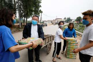 Father Francis Xavier Nguyen Duc Dai distributes food to local people while wearing a protective mask in Son Loi, Vietnam, Feb. 25, 2020. The area has been quarantined due to the coronavirus.
