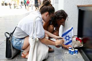 Israelis light candles near the site of a Palestinian shooting attack in Tel Aviv, Israel, June 9, 2016.