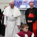 A child walks away after greeting Pope Francis during his visit to the Parish of San Cirillo Alessandrino in Rome Dec. 1. At right is Cardinal Agostino Vallini, papal vicar for Rome.