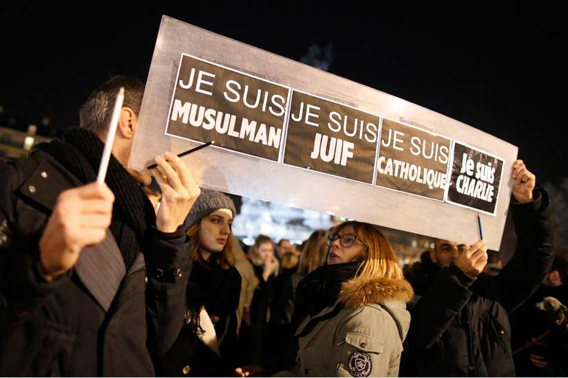 "People hold a placard that reads ""I am Muslim, I am Jewish, I am Catholic, I am Charlie"" during a Jan. 8 vigil in Paris, following the mass shooting at the offices of Charlie Hebdo, a satirical newspaper in Paris. Pope Francis condemned the killings of a t least 12 people at the offices of the publication Jan. 7 and denounced all ""physical and moral"" obstacles to the peaceful coexistence of nations, religions and cultures."