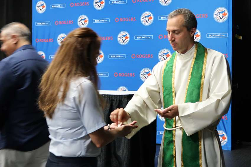 A young woman receives Holy Communion from Fr. Frank Portelli at the Rogers Centre Sunday Mass.