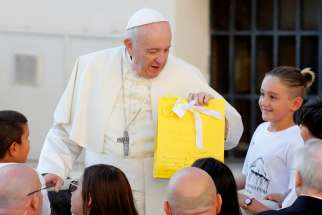Pope Francis receives a gift from children during his general audience in St. Peter's Square at the Vatican Sept. 11, 2019.