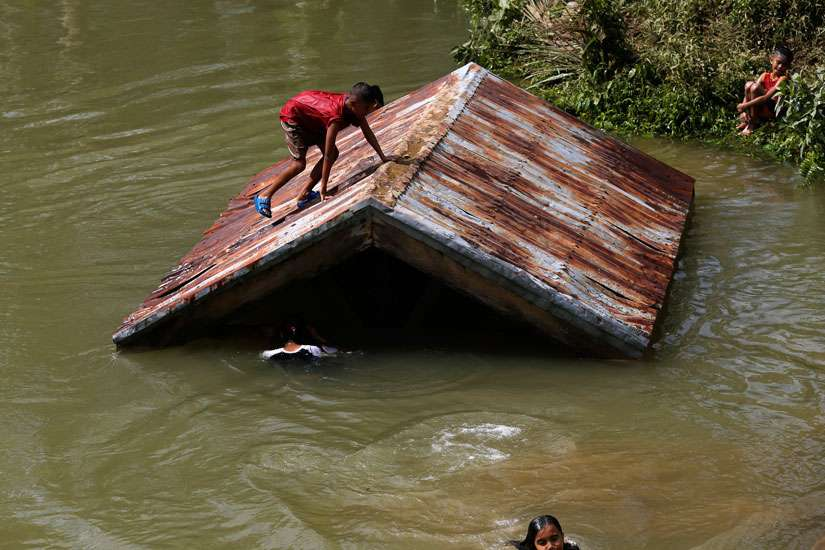 Children swim in a swollen river on Samar Island, Philippines, Dec. 8. Typhoon Hagupit weakened into a tropical storm after leaving at least 21 people dead and forcing more than a million people into shelters.