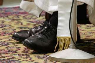 The shoes of Pope Francis are seen as he conducts a general audience in the Paul VI hall at the Vatican on March 16, 2013.