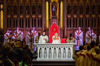 Cardinal Thomas Collins pours and rubs oil into the new altar at St. Michael's Cathedral, Sept 29.