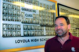 Paul Donovan, the recently retired president of Montreal's Loyola High School, stands by the graduating class photo that contains his father Kevin, who was also a student at the storied Jesuit high school.
