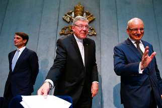 Jean-Baptise de Franssu, left, current president of the Vatican bank, former President Ernst Von Freyberg, right, and Australian Cardinal George Pell, prefect of the Vatican Secretariat for the Economy, leave at the end of a news conference at the Vatican July 9, 2014. The Vatican said it will separate its bank's investment business from its church payments work to try to clean up after years of scandal, including allegations of money laundering and tax evasion.