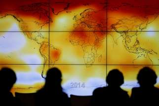 Participants look at a screen showing a world map with climate anomalies during the World Climate Change Conference at Le Bourge, France, in this Dec. 8, 2015, file photo.