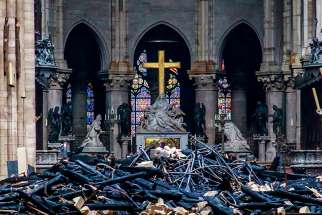 Debris surrounds a depiction of the Pieta by Nicolas Coustou in Notre Dame Cathedral April 16, 2019, a day after a fire destroyed much of the church's wooden structure. Officials were investigating the cause of the blaze, but suspected it was linked to renovation work that started in January.