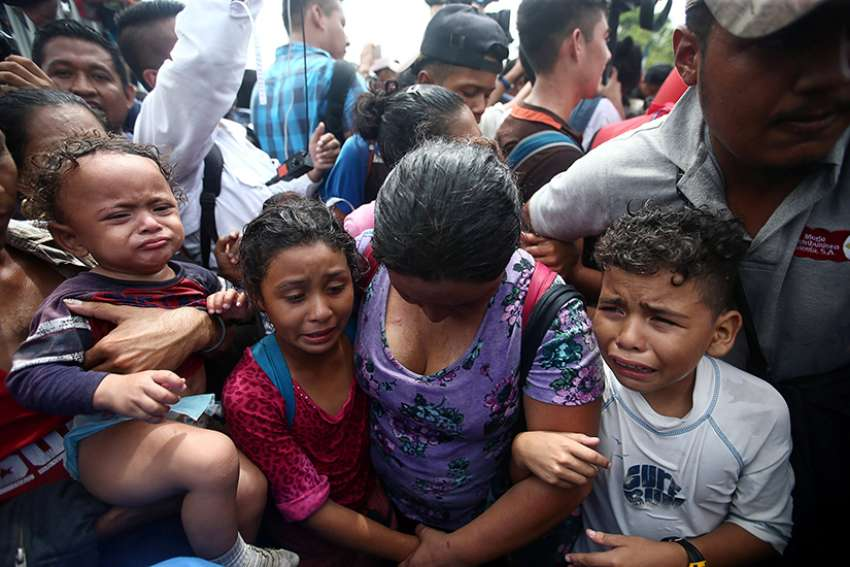 Children cry next to their mother after a caravan of Honduran migrants trying to reach the U.S. stormed a border checkpoint Oct. 19 in Ciudad Hidalgo, Mexico.