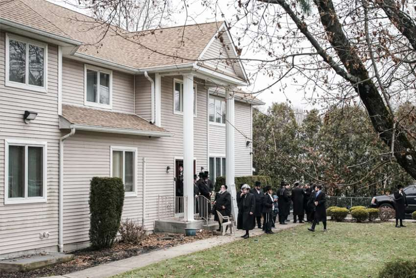 People gather at Rabbi Chaim Rottenberg's residence in Monsey, N.Y., Dec. 29. A machete-wielding man attacked the residence during a Hanukkah celebration the night before.
