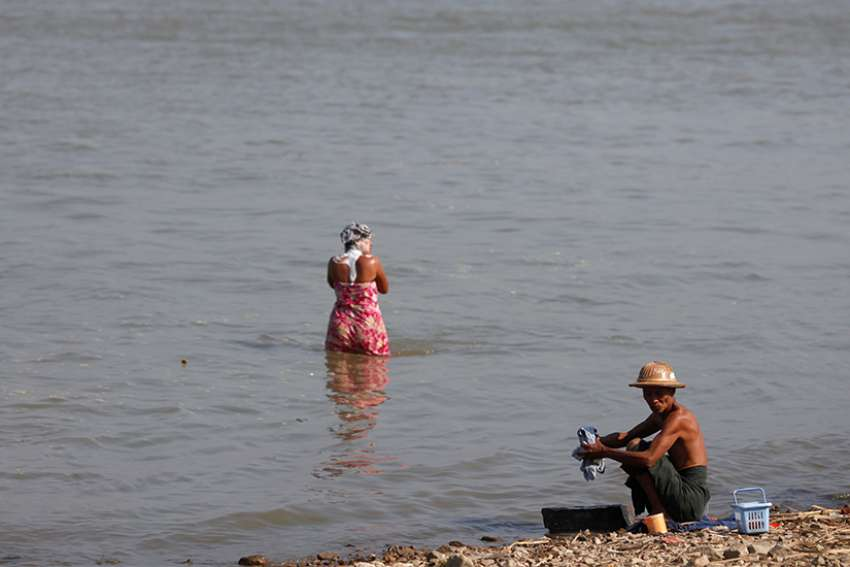 "A man washes clothes and a woman washes her hair along the bank of the Irrawaddy River in Sagaing, Myanmar, March 4, 2012. The Irrawaddy River is ""our mother"" and is at risk of being lost ""to the greed of a superpower,"" Cardinal Charles Maung Bo of Yangon said in a Jan. 28 statement."