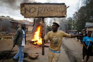 "A supporter of the opposition leader Raila Odinga reacts as he holds up a sign that reads ""No Raila, No Peace"" during an Aug. 9 protest in Nairobi, Kenya. Catholic bishops in Kenya called for calm in the East Africa nation, as pockets of violent post election protests left at least five dead in opposition strongholds."
