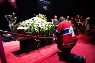 A mourner kneels in front of the casket of Jean Beliveau as he pays his respects to the Montreal Canadiens hockey legend during a public viewing in Montreal Dec. 7.