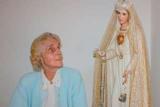 Natalie Martha Loya, pictured in an undated photo, gazes at a statue of Our Lady of Fatima that crisscrossed the country with her during her 35-year apostolate of spreading the Fatima message.