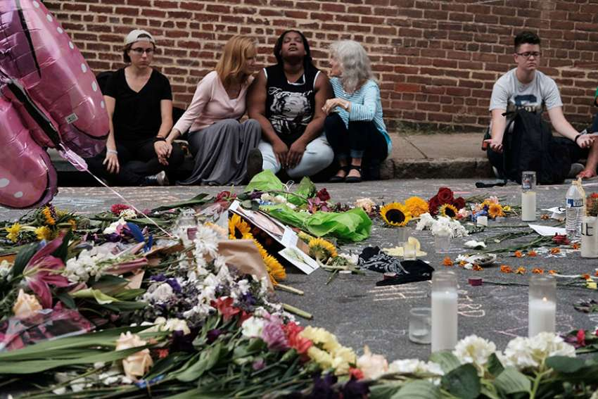 People sit by a memorial of flowers in Charlottesville, Va., Aug. 14 where an Aug. 12 car attack took place against counter-protesters demonstrating at a rally of white nationalists.