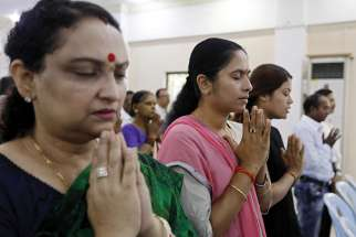 Hindu women pray for peace Oct. 1 at the Sri Bunar Maha Shiva Hindu temple in Yangon, Myanmar. Peace and harmony will not result from members of different religions simply tolerating each other; respect and appreciation of customs and cultural diversity is required, top Vatican officials said in a message to the world's Hindus.