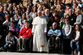 Pope Francis poses with people during his general audience in St. Peter's Square at the Vatican Oct. 12. Pope Francis told thousands of grandparents in a belated celebration of Italy's Grandparents' Day Oct. 15 that they must uphold values that bring hope and wisdom to younger generations.