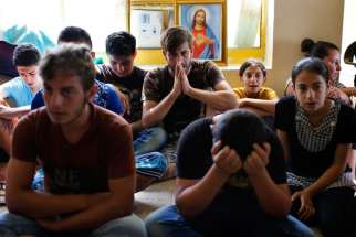 Displaced Iraqi Christians who fled from Islamic State militants in Mosul pray at a school acting as a refugee camp in Irbil, Iraq, Sept. 6. Irbil now hosts more than 100,000 displaced Christians and other minorities. Some Christians who have fled Iraq say they do not want to return