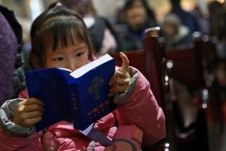 A girl reads a Bible during Mass in the state-approved Xuanwumen Catholic Church in Bejing, China, Dec. 4, 2016. While the Chinese government technically recognizes Catholicism as one of five religions in the country, it does not recognize many Church leaders appointed by the Vatican, driving many among the Catholic Church leadership and laity underground.