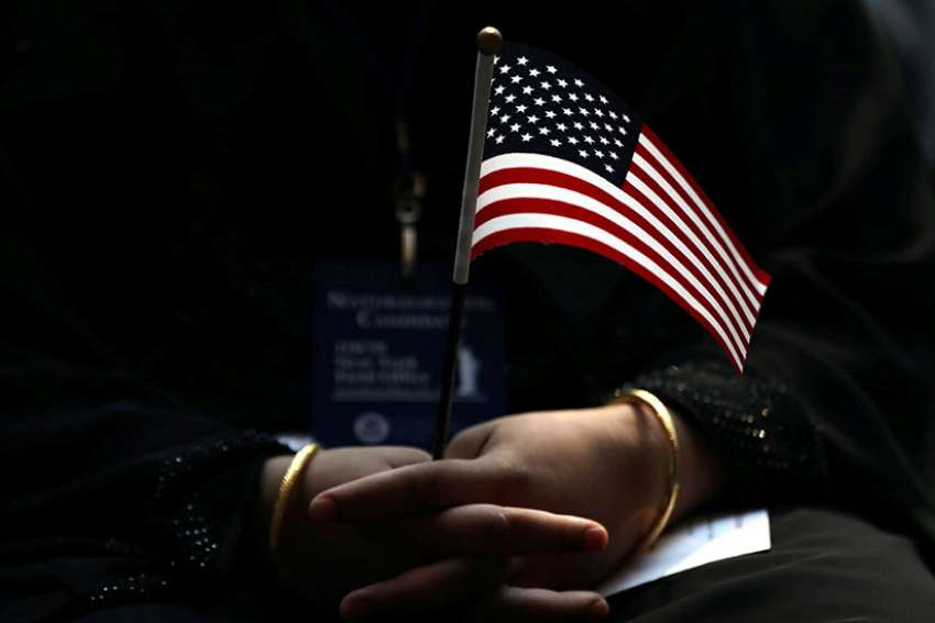 An immigrant holds a U.S. flag during a naturalization ceremony in New York City June 30.