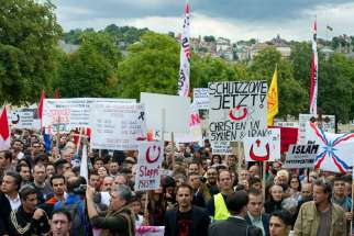 "Protesters in Stuttgart, Germany, rally during an Aug. 23 demonstration initiated by the Syrian Orthodox Church in solidarity with religious minorities threatened in Northern Iraq and throughout the Middle East. The Franciscan custos of the Holy Land sai d force alone cannot stop ""religious cleansing"" in the Middle East."