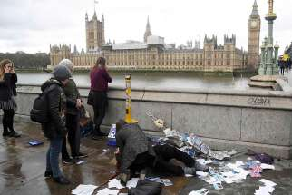 An injured woman is assisted after an attack on Westminster Bridge in London March 22.