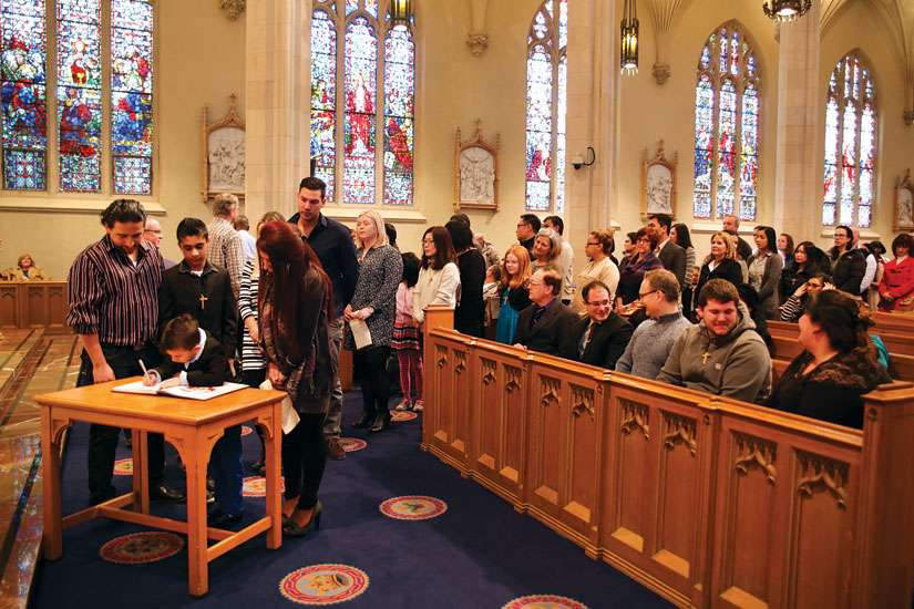 Catechumens and their sponsors line up to sign the book at the Rite of Election during the First Sunday of Lent at the Cathedral Basilica of Christ the King in Hamilton.