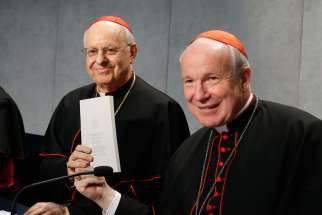 "Cardinal Lorenzo Baldisseri, general secretary of the Synod of Bishops, and Austrian Cardinal Christoph Schonborn, holds a copy of Pope Francis' apostolic exhortation on the family, ""Amoris Laetitia"" (""The Joy of Love""), during a news conference for the document's release at the Vatican April 8. The exhortation is the concluding document of the 2014 and 2015 synods of bishops on the family."