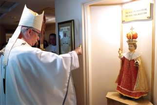 Edmonton Archbishop Richard Smith blesses the 500-year-old statue donated to the Discalced Carmelites.