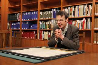 UBC history professor Richard Pollard studies a papal bull that was issued by Pope Innocent IV and 13 cardinals in Lyons in 1245. The parchment is now stored in a vault at the university.