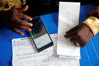 An official of the Congolese Independent National Electoral Commission uses his phone to calculate the numbers of presidential election votes at a tallying center in Kinshasa Jan. 4, 2019. Catholic leaders in Congo have gathered more than 1.5 million signatures on a petition that demands local elections to curb corruption and strengthen democracy.